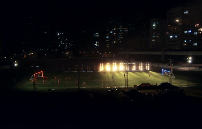 A creatively lit football stadium screenshot from a sports social campaign