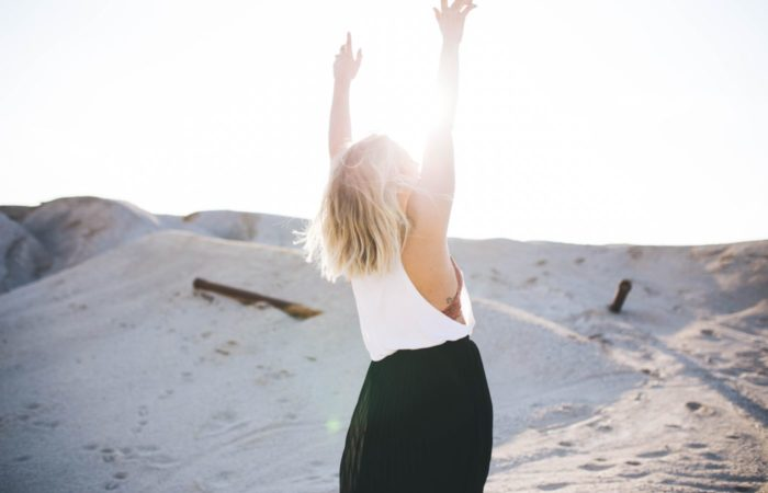Woman on a beach facing away from the camera, her arms up as the sun hits her
