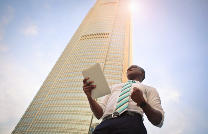 A businessman holding an iPad, clenching his fist and looking motivated, a highrise building behind him