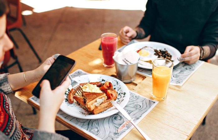 Person taking a photo of their brunch at a café representing ideal user generated content.